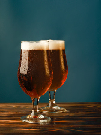 Two glasses with a light beer on a wooden table and blue background.