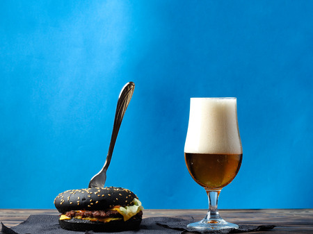 A set of beer and a hamburger on a wooden table. Stock Photo