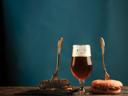 A traditional and black burger on a wooden table and with glasses full of foamy light beer.