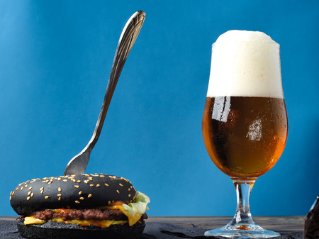 A set of beer and a hamburger on a wooden table. Black hamburger and light beer.