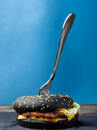 black hamburger with fork on a blue background. Stock Photo