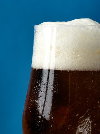 A glass of beer with a close-up on a blue background.