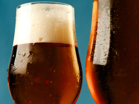 Two mugs of beer on a blue background.