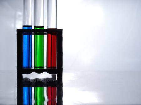 Test tubes with blue, green and red liquid in a rack for test tubes on a white table and a white background. The chemists table. Фото со стока