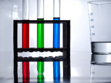 Test tubes with blue, green and red liquid in a rack for test tubes and a measuring glass on a white table and a white background.