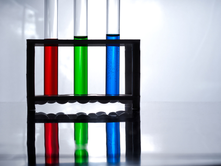 Test tubes with blue, green and red liquid in a rack for test tubes on a white table and a white background. The chemists table. The chemists table.