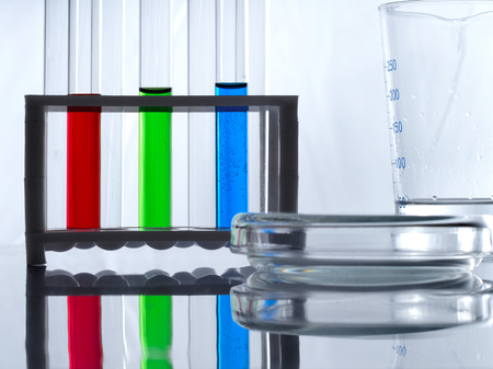Test tubes with blue, green and red liquid in a tube rack, measuring cup and a petri dish on a white table and white background. Biologists desk.