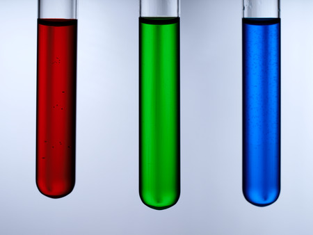 Test tubes with reagents on a white background. A test tube with a red, green and blue liquid on a white background. Фото со стока