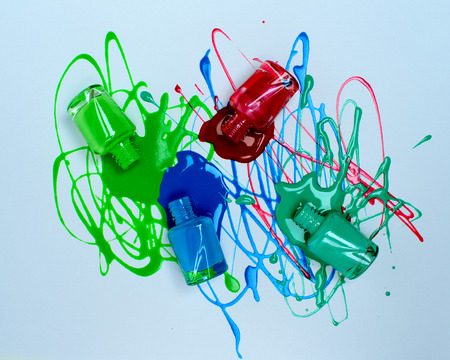 spray of green, blue, red and turquoise nail polish on white paper. Reklamní fotografie