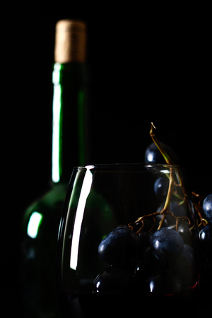Wine and grapes on a black background.
