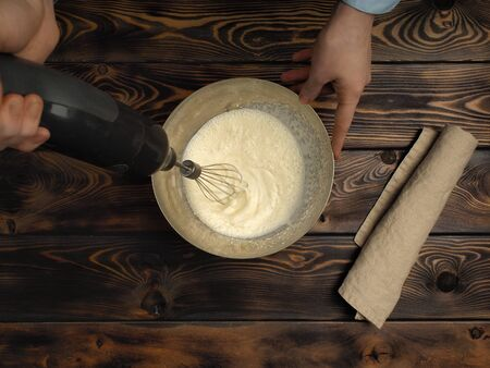 Recipe of cooking of a dessert of Tiramisu, part fourth: Whipping Cream. Products on a wooden table: fat cream. Reklamní fotografie