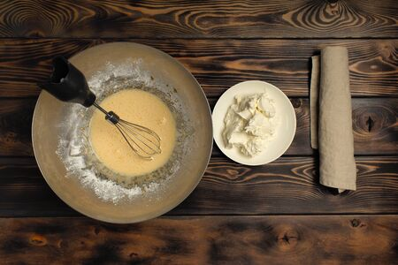 Recipe of cooking of tiramisu, part third: To mix egg weight with mascarpone. Products on a wooden table: the mascarpone cheese, the shaken-up mix of egg yolks, wire whisk. Reklamní fotografie