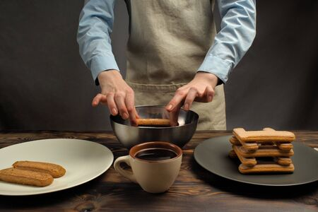 Recipe of cooking of a dessert of tiramisu, part sixth: Biscuit impregnation in coffee. Products: Strong coffee and Ladyfinger biscuit.