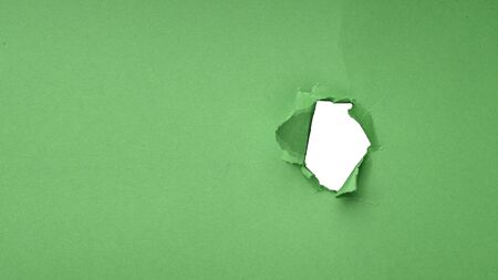 A hole in a green sheet of paper. 写真素材 - 124695409