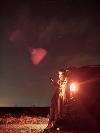 Night landscape in the light of car headlights. A woman stands at night against the starry sky in the light of car headlights and uses in the phone. Reklamní fotografie