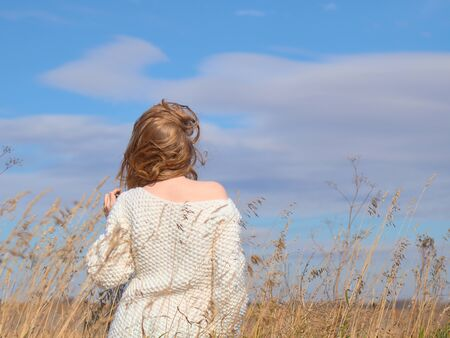 Beautiful pregnant woman in a white woolen sweater. Pregnant woman hugs belly in the field. Banco de Imagens