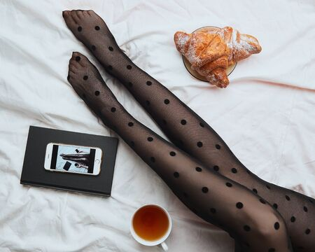 Stylish, trendy morning light breakfast on the bed. top view, legs of a girl dressed in polka-dot stockings, on a bed with a notepad, a smartphone, croissants and a mug of tea.