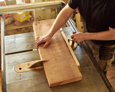 Sawing the board for the subsequent manufacture of the fretboard of a classical guitar. Reklamní fotografie