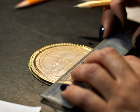 The engraver places a marking on the medal over the paste.