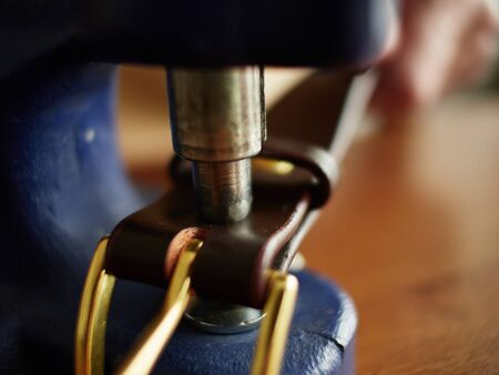 Riveting the brass belt buckle.