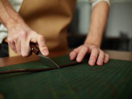 Cutting the edge of the workpiece with a tailor knife.
