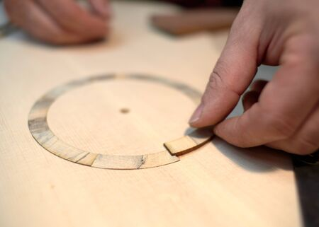 The guitar master pastes the rosette into a classical guitar.