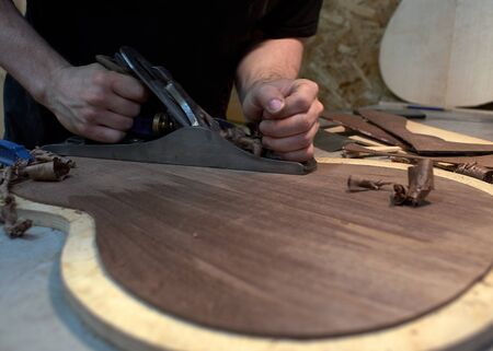 The guitar master scribbles back of the future classical guitar with a plane.