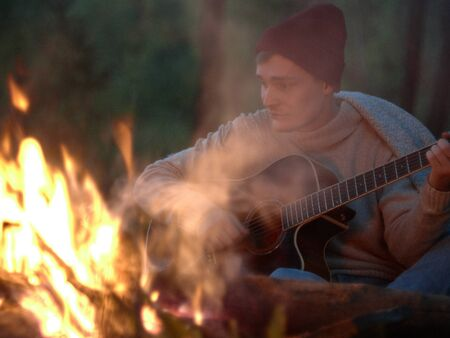 Camping at night around a campfire in nature to the sound of a guitar. A young guy in a gray sweater and red cap sits around a fire and plays the guitar. Фото со стока