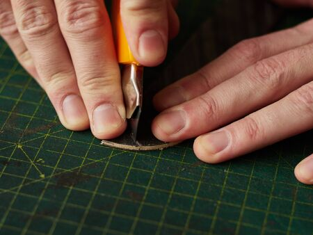 Shaping the tip of the leather strap with a knife.