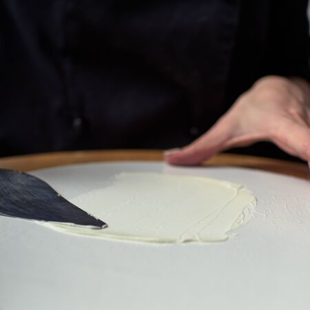 Step-by-step preparation of black designer cake. The confectioner covers the cake with cream. Stok Fotoğraf
