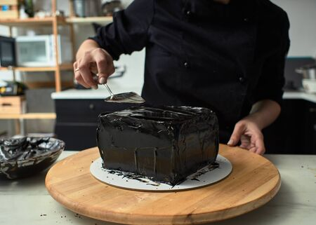 Step-by-step preparation of black designer cake. The confectioner is applying a black frosting on the cake. Stok Fotoğraf