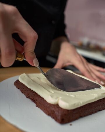 Step-by-step preparation of black designer cake. The confectioner covers the cake with cream. Stock fotó