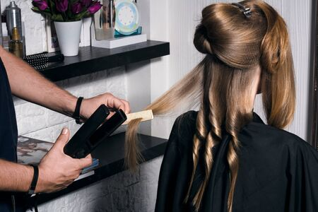 Young woman doing hair styling in the salon. Curls the hair in a spiral.