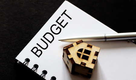 Business Words on notepad, business tex Budget with woooden house and pen