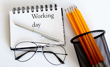 Notepad and text Working day and yellow pencil, pen and glasses