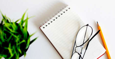 blank notebook with glasses and pencil on wooden table, business concept 版權商用圖片