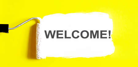 WELCOME. One open can of paint with white brush on it on yellow background. Top view. 스톡 콘텐츠