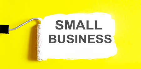 SMALL BUSINESS. One open can of paint with white brush on it on yellow background. Top view. Repairing concept.