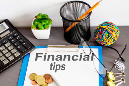 FINANCIAL TIPS written on paper with office tools Banque d'images