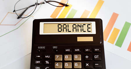 calculator with the word BALANCE on display with chart and glasses