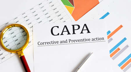 Paper with Corrective and Preventive CAPA action plans on table