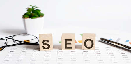 SEO word concept written on wooden blocks, cubes on light table with flower, pen and glasses on chart background