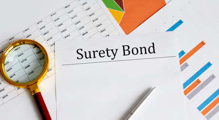 Paper with Surety Bond on table with pen, chart and magnifier