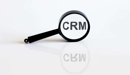 Magnifier with text CRM on white background
