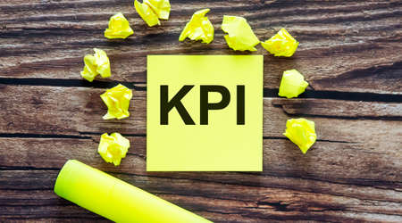KPI. Notes about KPI, concept on yellow stickers on wooden background