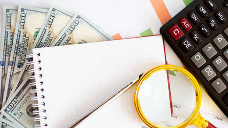 Conceptual image with hundred dollar bills, calculator, notepad and magnifying glass on chart