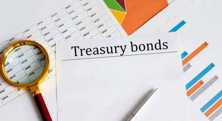 Paper with Treasury bonds on a table with charts, magnifier and pen