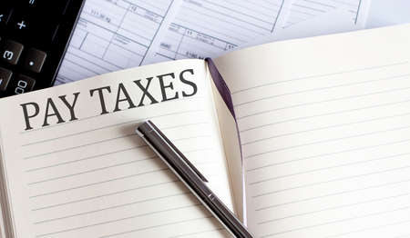 Notebook with Toolls and Notes about PAY TAXES. Business Imagens