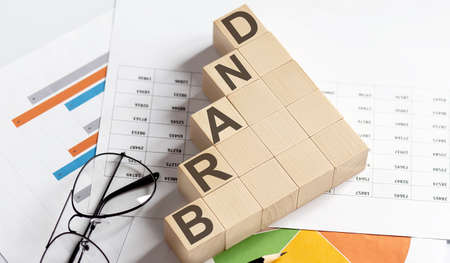 BRAND words with wooden blocks on chart background. Business concept.