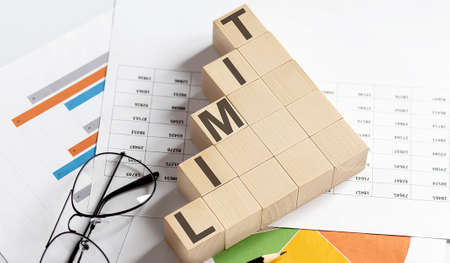 LIMIT words with wooden blocks on chart background. Business concept.